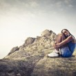Young african woman sitting on a rock — Stock Photo