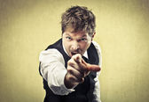 Angry man pointing his finger against somebody — Stockfoto