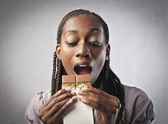 African woman eating a chocolate bar — Stock Photo