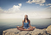 Beautiful african woman sitting on a peak over the sea and meditating — Stock Photo
