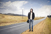 Young man standing on a country road — Stock Photo