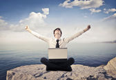 Triumphing young businessman sitting on a peak over the sea with a laptop on his knees — Stock Photo