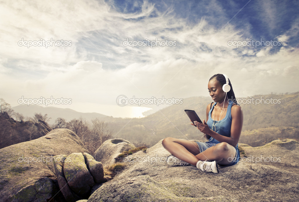 Smiling african woman sitting on a rock and using a tablet pc — Stock Photo #10627836