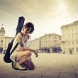 Beautiful young woman on a town square carrying a guitar case on her shoulders — Stock Photo