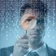 Young businessman observing a binary code on a screen through a magnifying glass — Foto de Stock