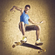 Stock Photo: Smiling young man skateboarding