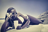 Beautiful african woman lying on a beach and having a refreshing drink — Stock Photo
