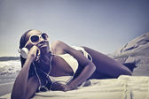 Beautiful african woman lying on a beach and listening to music — Stock Photo