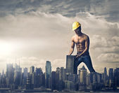 Young brawny worker settling a skyscraper in the skyline of a big city — Foto de Stock