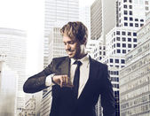 Smiling young businessman looking at his wristwatch with cityscape in the background — Stock Photo