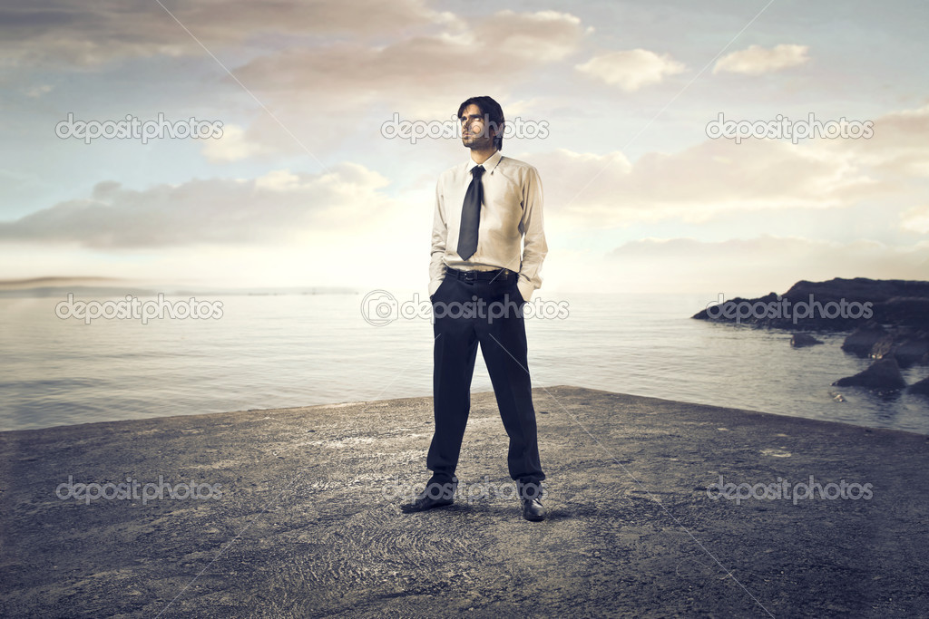 Young businessman standing on a beach — Stock Photo #10694628
