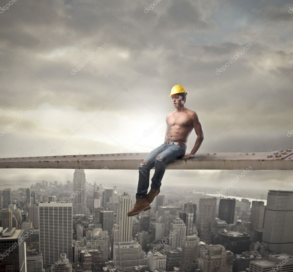 Young brawny worker sitting on a metal bar over a big city  Stock Photo #10694645