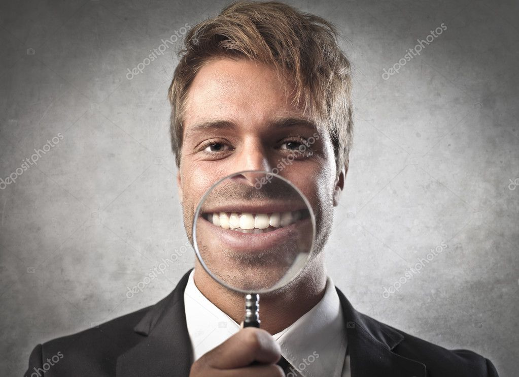 Young businessman zooming on his smile with a magnifying glass  Foto Stock #10694718