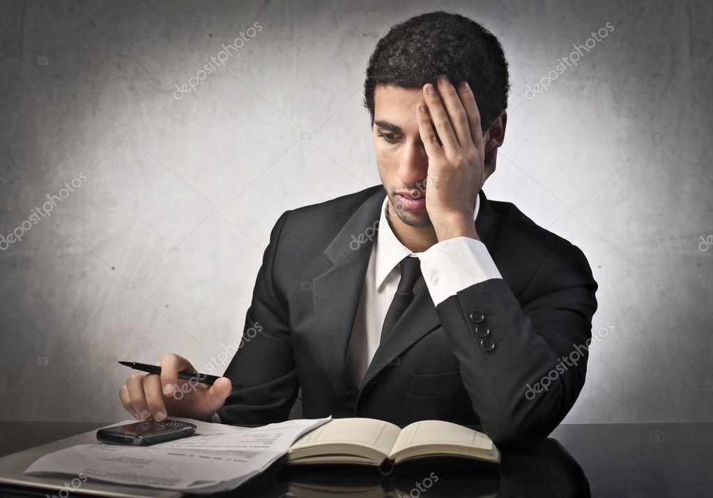 Worried businessman writing the closing balance — Stock Photo #8693569