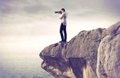 Youg photograph taking pictures from a rock over a sea — Stock Photo