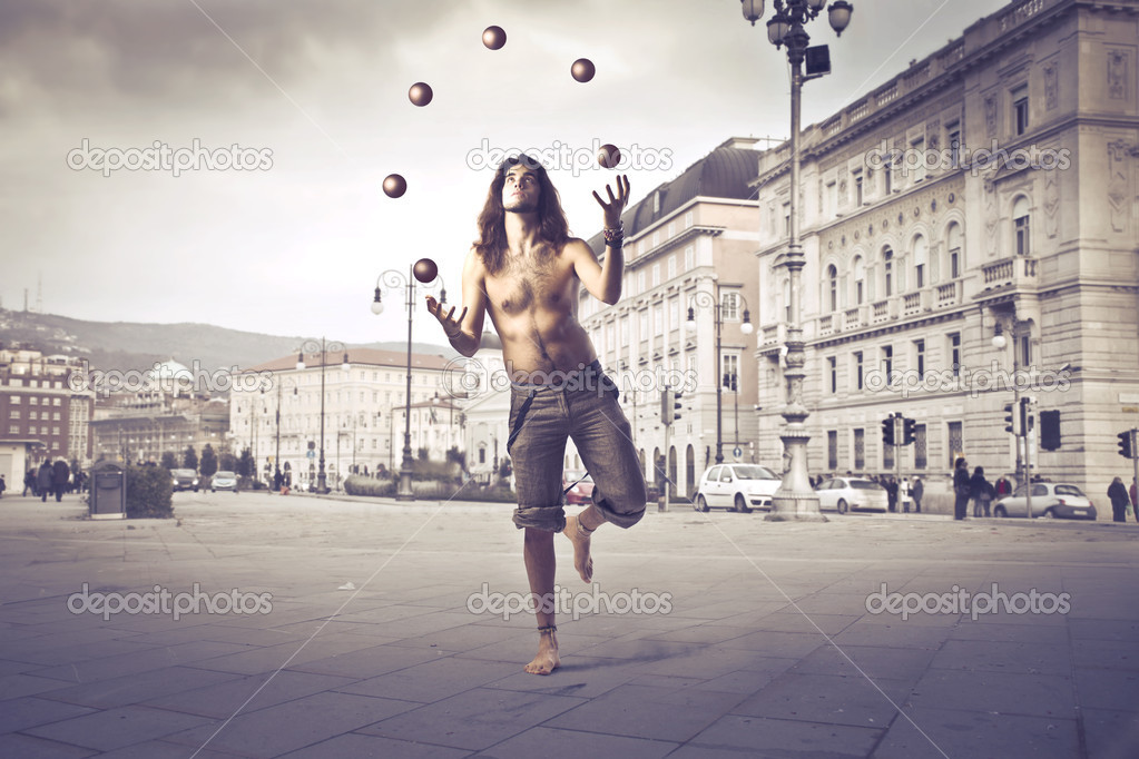 Young man juggling on a city square  Stock Photo #9059655