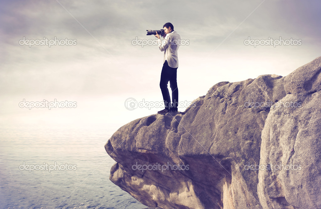 Youg photograph taking pictures from a rock over a sea — Stock Photo #9059849