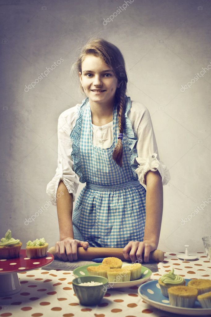 Smiling pretty teenage girl baking cookies  Stock Photo #9086888