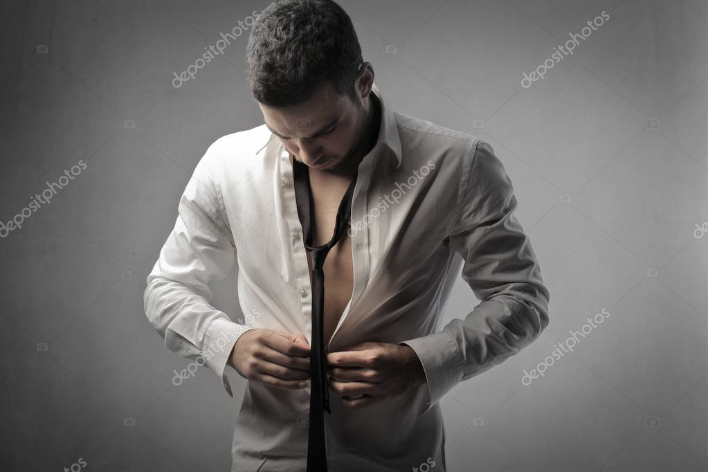 Handsome young man putting on a shirt  Stock Photo #9229345