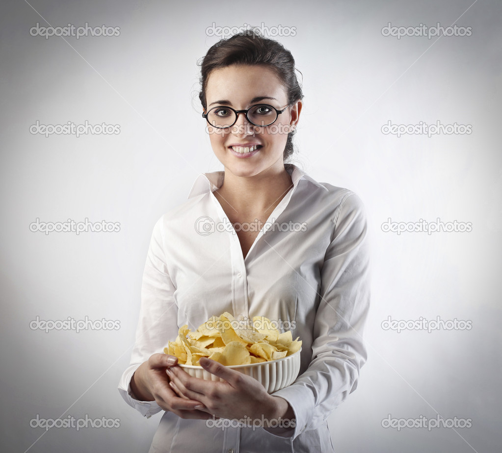 Smiling businesswoman holding a bowl of potato chips  Stock Photo #9399168