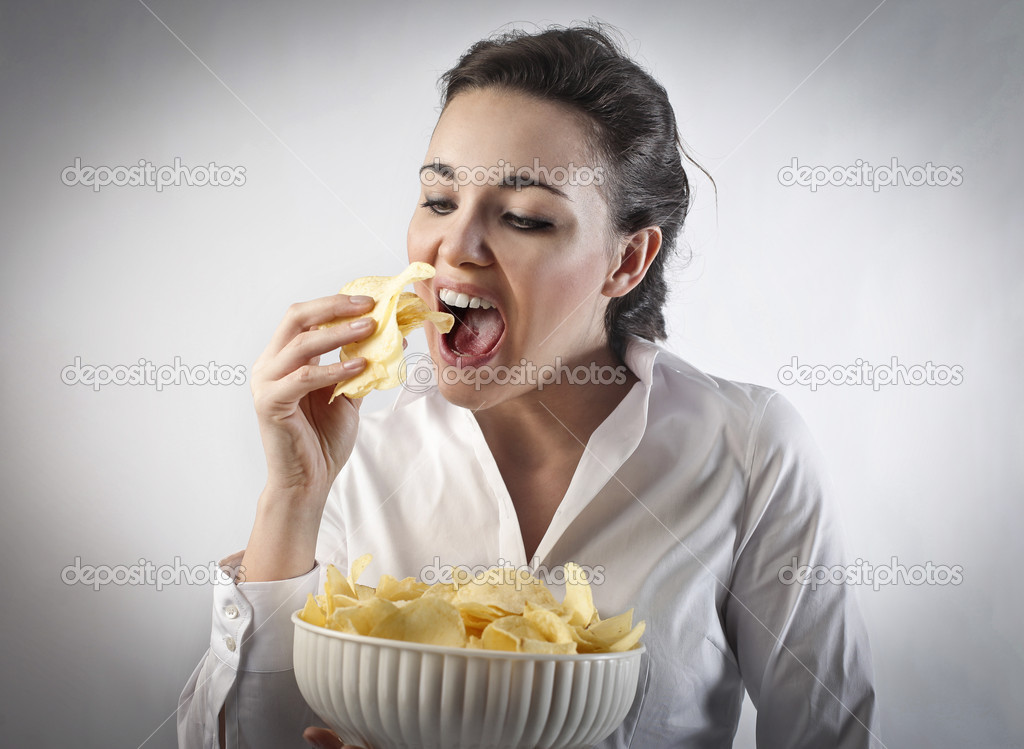 Young woman eating potato chips from a bowl — Stock Photo #9399265