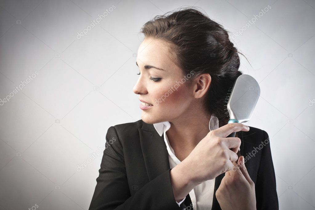Smiling beautiful businesswoman brushing her hair — Stock Photo #9399407