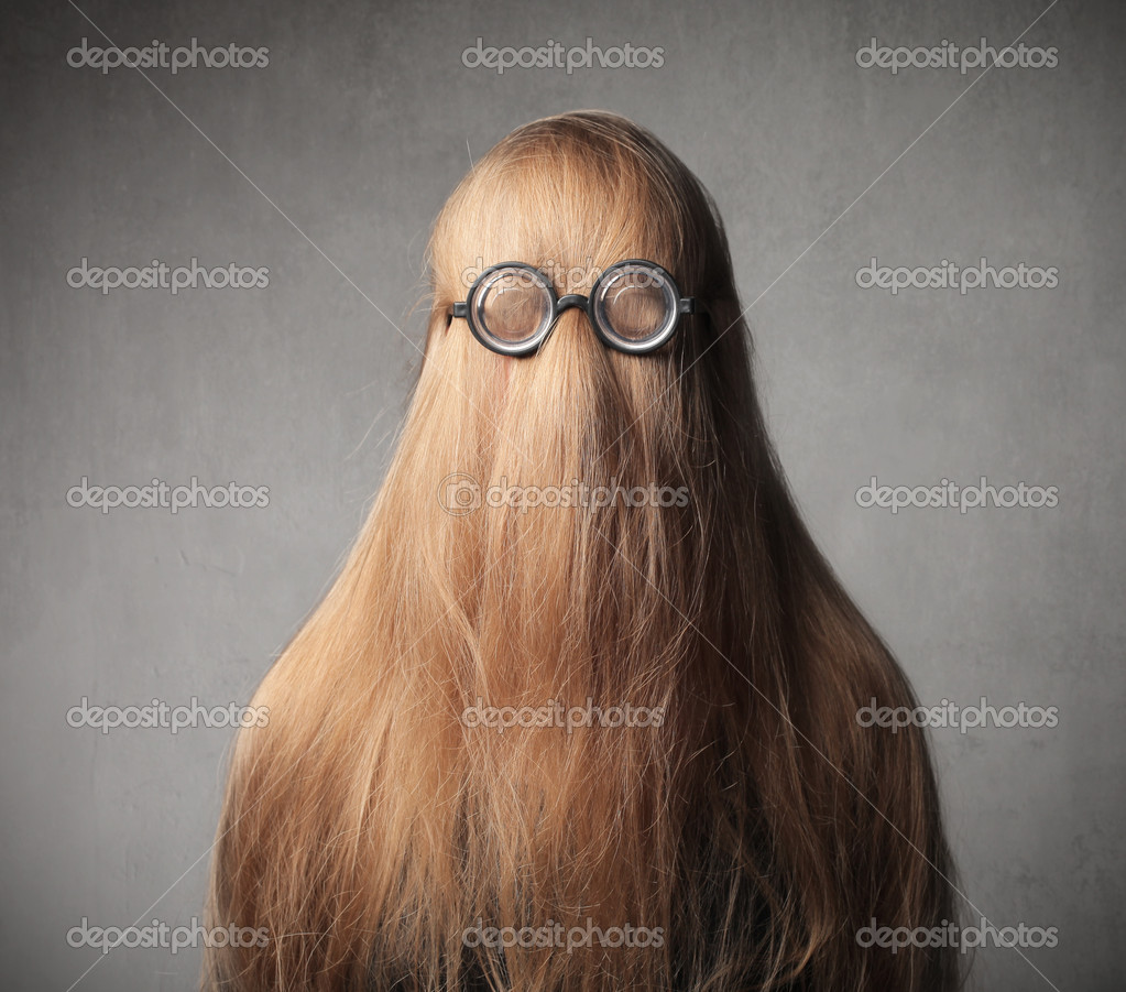 Teenage girl with her hair on her face wearing eyeglasses — Stock Photo #9677328