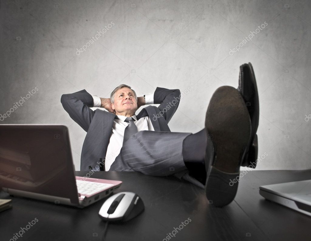 Senior businessman relaxing on his chair at the office  Stock Photo #9754744