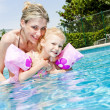 Mother with her daughter in swimming pool - Stock Photo