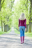 Woman wearing rubber boots in spring alley — Stock fotografie