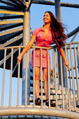 Young woman wearing pink dress standing on stairs of lookout tow — Stock Photo