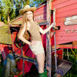 Young woman standing by old threshing machine — Stock Photo #10480850