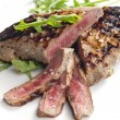 Grilled beefsteak pickled in Dijon mustard with ruccola - Stock Photo