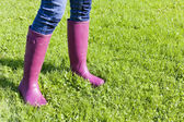 Detail of woman wearing rubber boots on lawn — Stock Photo