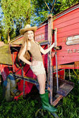 Young woman standing by old threshing machine — ストック写真