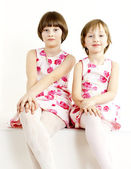 Two sisters wearing similar dresses — Stock Photo