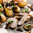 Stock Photo: Pork tenderloin baked on mushrooms