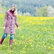 Stock Photo: Womwearing rubber boots standing on spring meadow