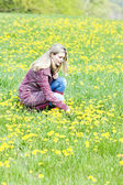 Woman sitting on spring meadow — Stock Photo
