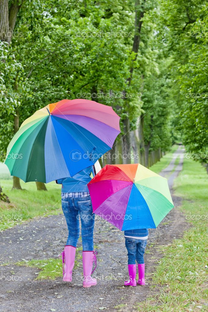 Mother and her daughter with umbrellas in spring alley — Stock Photo #8743540
