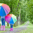 Mother and her daughter with umbrellas in spring alley — Stock Photo #8826817