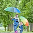 Mother and her daughter with umbrellas in spring alley — Stock Photo #8826821