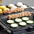 Meat skewers and vegetables on electric grill — Stock Photo