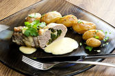 Baked pork tenderloin filled with spinach and goat cheese on cre — Stock Photo