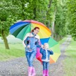 Mother and her daughter with umbrellas in spring alley — Stock Photo #9544611