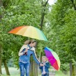 Mother and her daughter with umbrellas in spring alley — Stock Photo #9544615