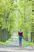 Woman wearing rubber boots in spring alley — Stock Photo