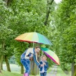 Mother and her daughter with umbrellas in spring alley — Stock Photo