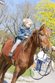 Little girl on horseback — Stock Photo