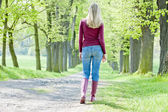 Woman wearing rubber boots walking in spring alley — Stock Photo